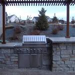 Outdoor Kitchen with Chilton Stone Veneers & Indiana Limestone Coutertops with a Pergola.